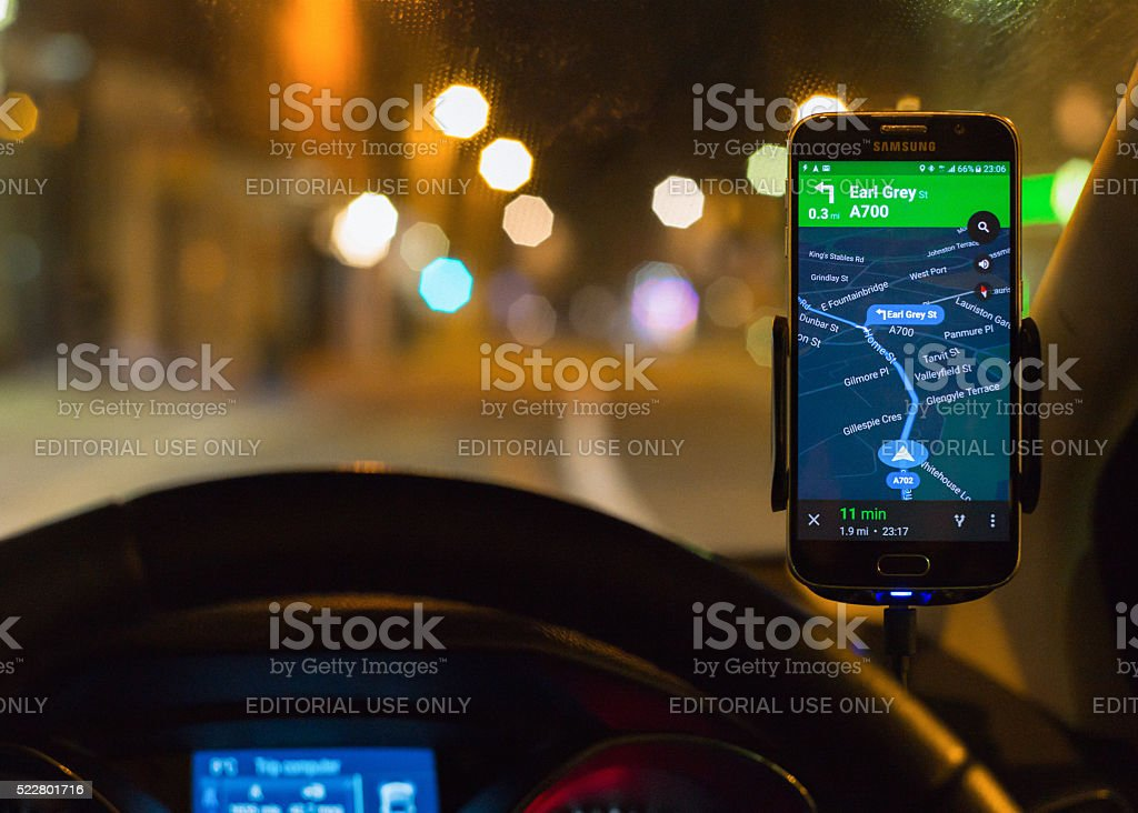 Using smartphone SatNav at night for driving directions. stock photo