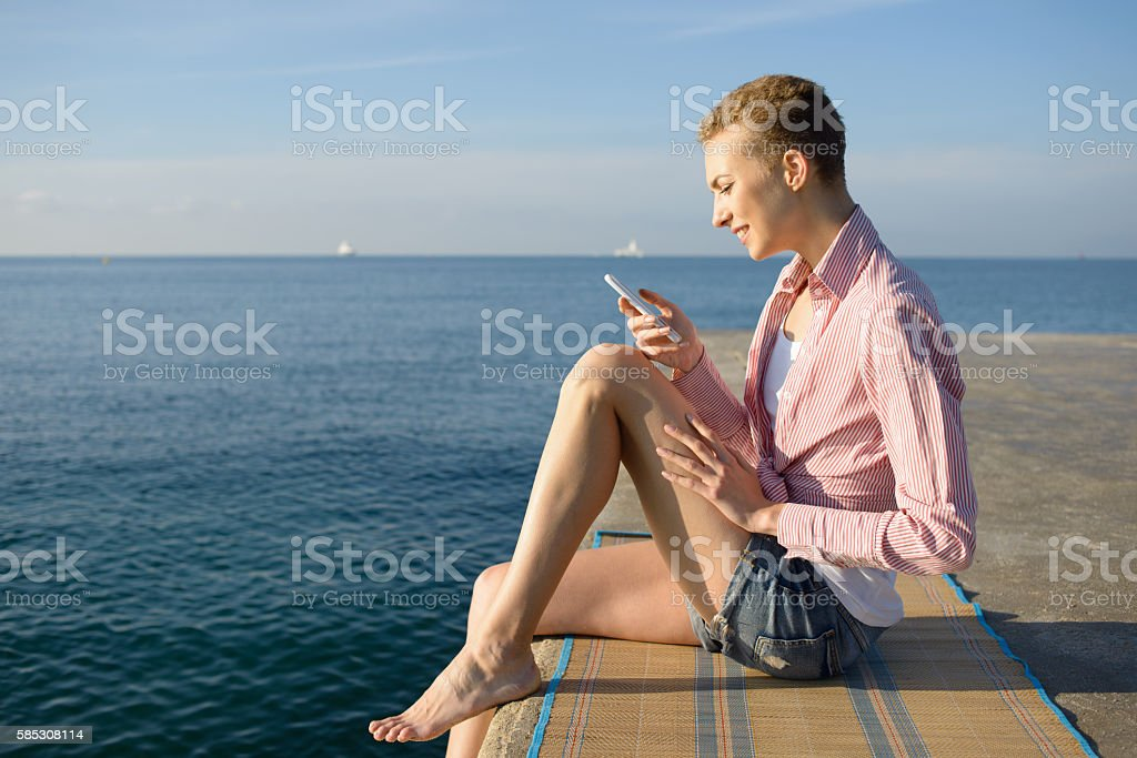 Using Smartphone Sitting by Sea at Dawn in Summer stock photo