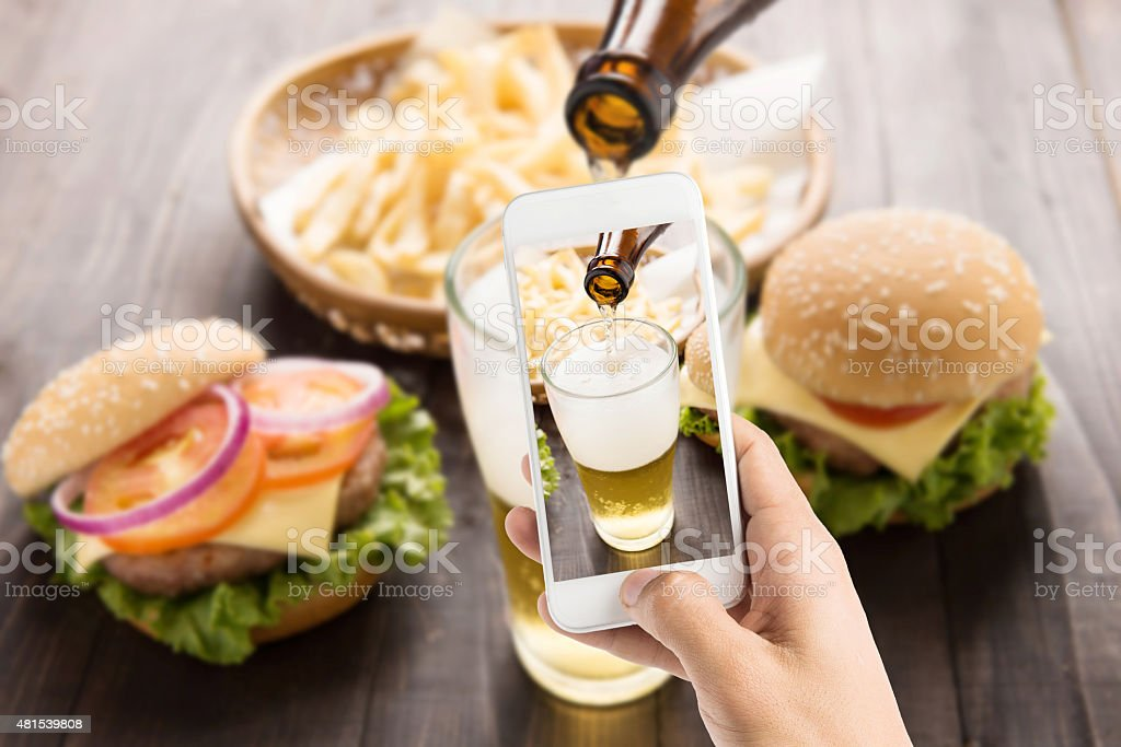 Using smartphones to take photos beer being poured into glass stock photo