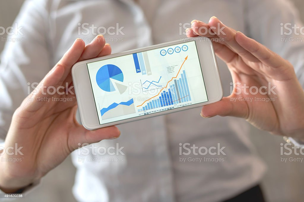 Using statistics business app on a cell phone stock photo