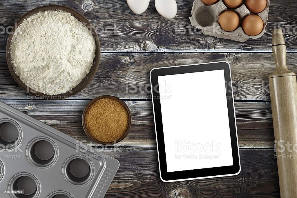 Using Tablet pc for Pastry receipe stock photo