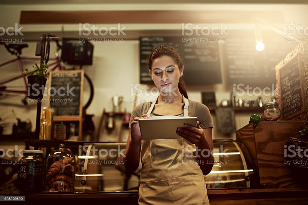 Using technology to streamline daily coffee shop related tasks stock photo