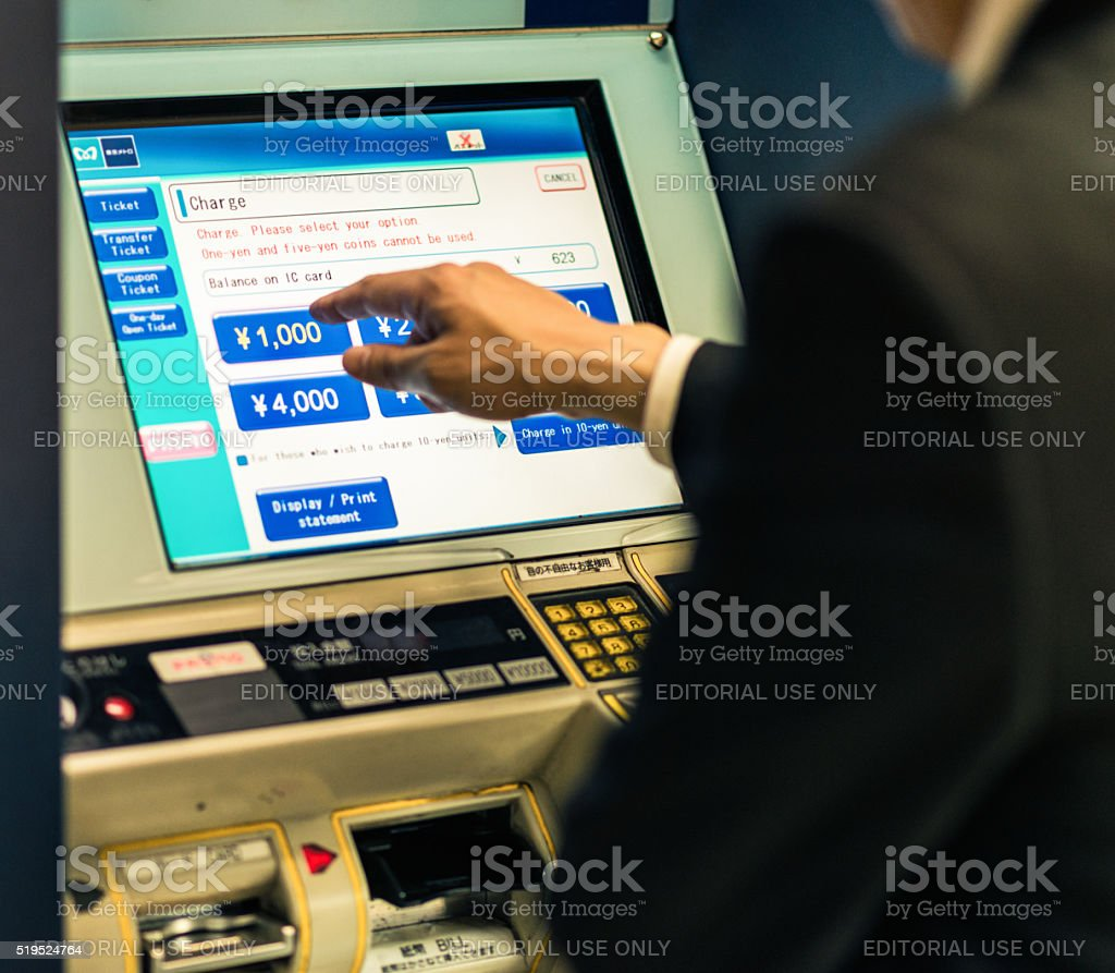 Using teller machine to re-charge IC transport card in Tokyo stock photo