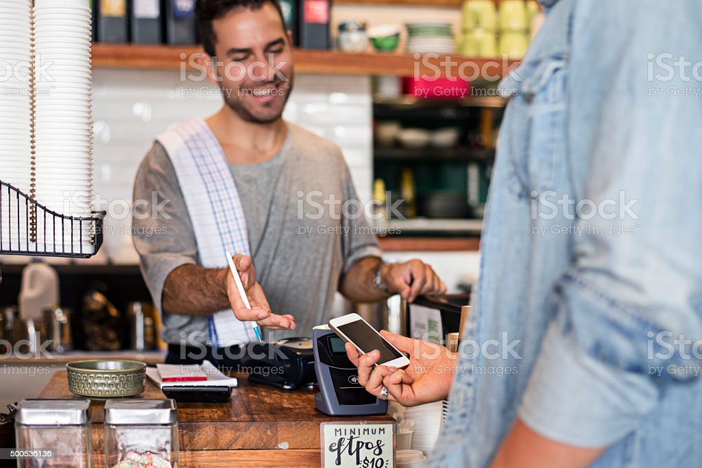 Using the contactless mobile phone payment in the cafeteria stock photo