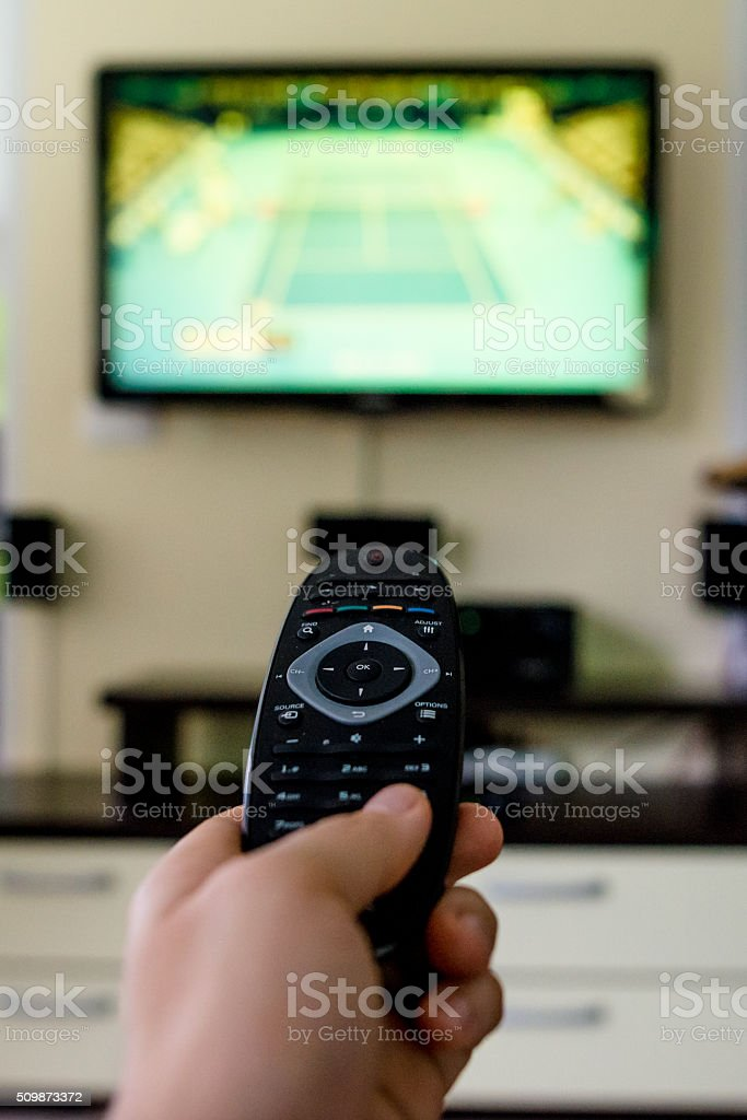 Using the remote control to change channel on TV stock photo