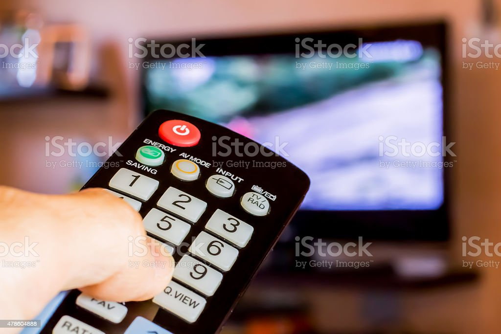 Using the remote control to change channesl on Tv stock photo