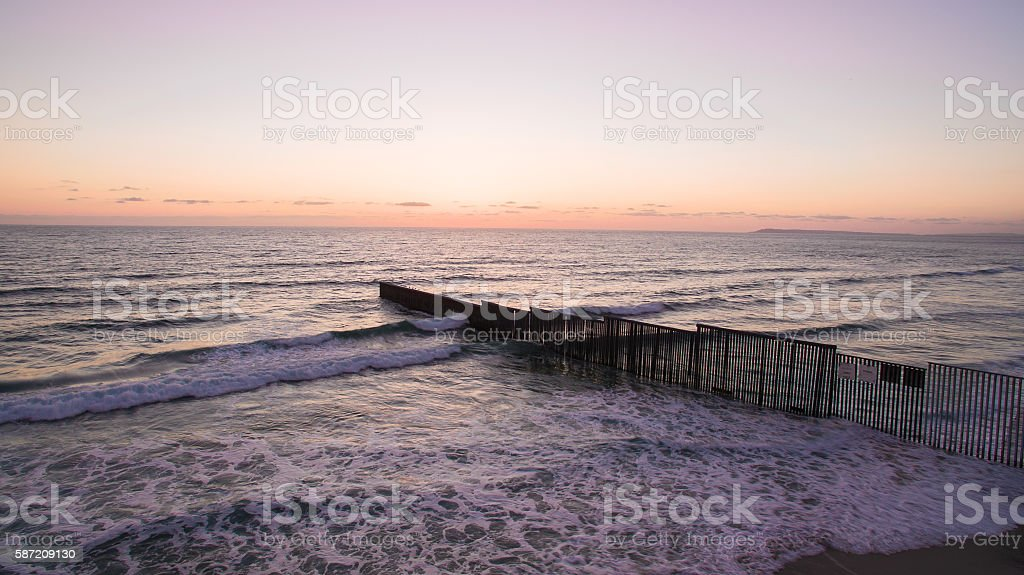 US/Mexico Border Fence in the Ocean Sunset stock photo