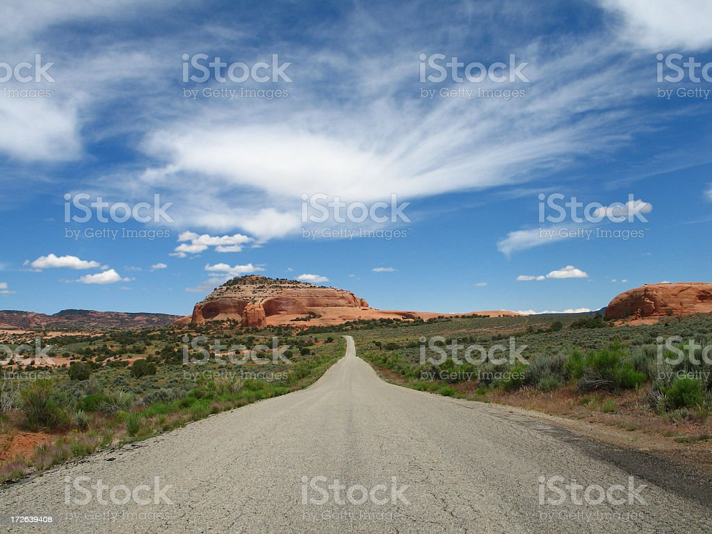 Utah Landscape: Red-Rock Formation and Road Beneath a Desert Sky royalty-free stock photo