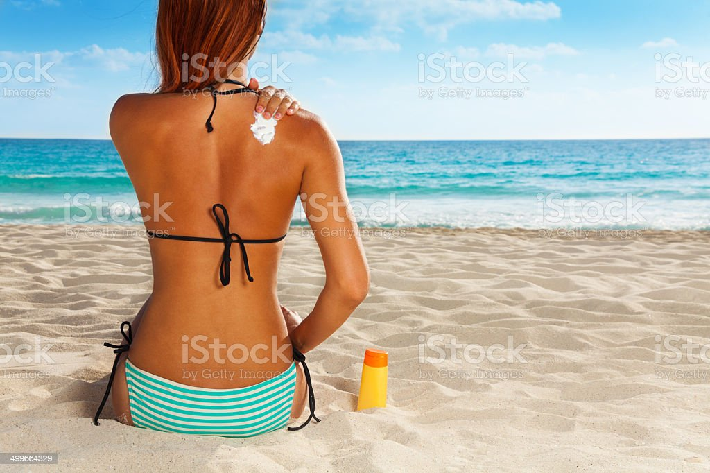 Ð¡ute girl's back with sunscreen on it stock photo