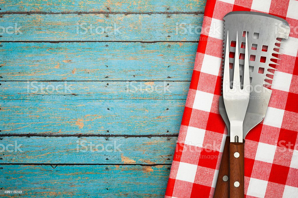 BBQ Utensils on Blue Rustic Picnic Table stock photo
