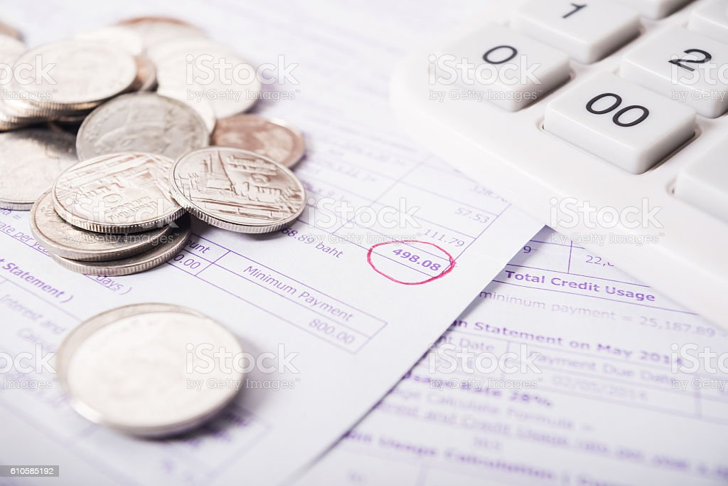 Utility bill with silver coins and calculator stock photo