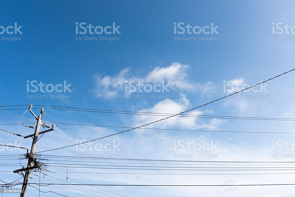 Utility Pole and Electrical Cables Through Blue Sky stock photo