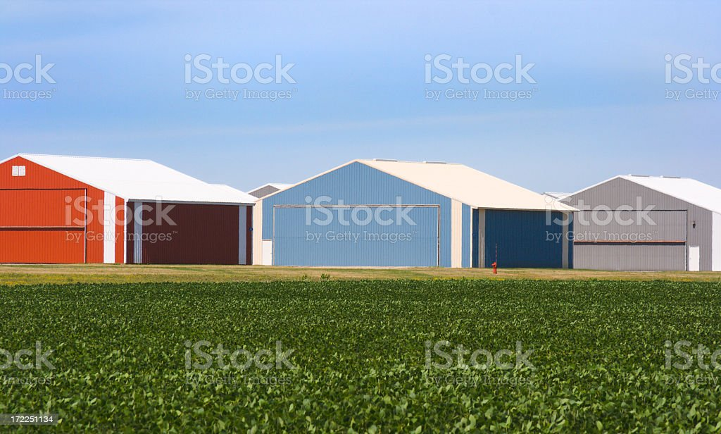 Utility Storage Buildings by Green Summer Fields Under Blue Sky stock photo