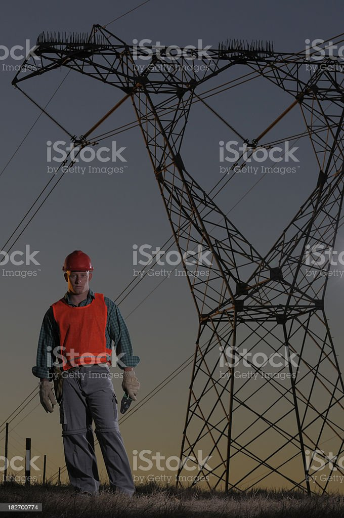 Utility worker against power pylons wide royalty-free stock photo