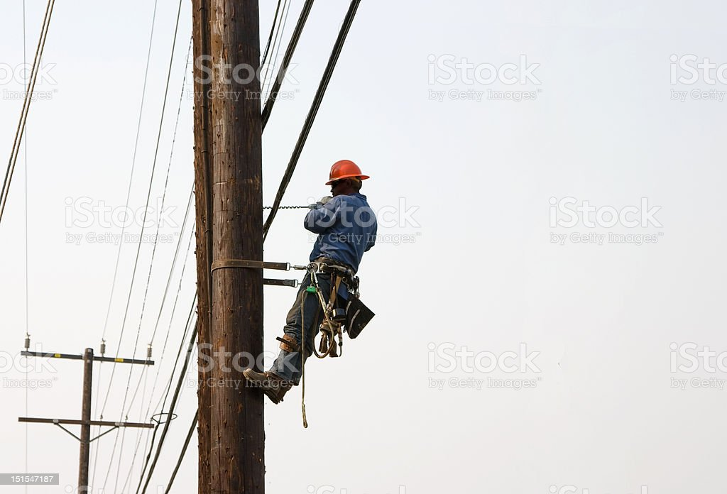 Utility worker drilling hole while suspended in air stock photo