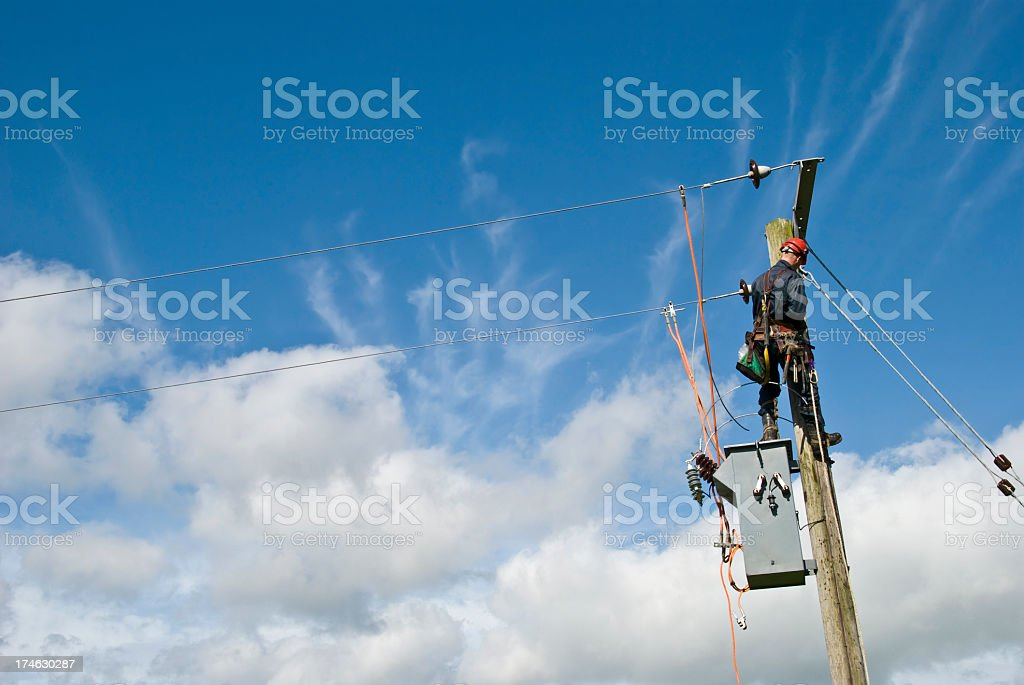 Utility worker repairing power lines under a blue sky stock photo