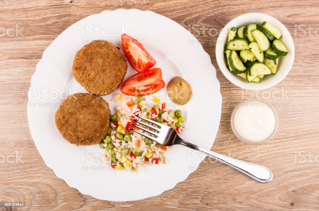 Сutlets with vegetable mix, tomatoes and mustard in plate, cucumbers stock photo
