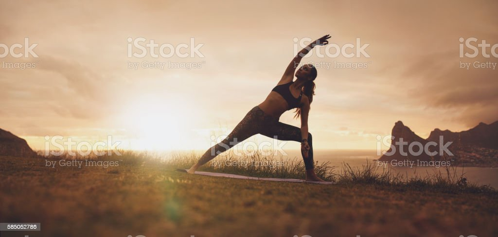 Utthita Parsvakonasana yoga asana on the cliff at sunset stock photo