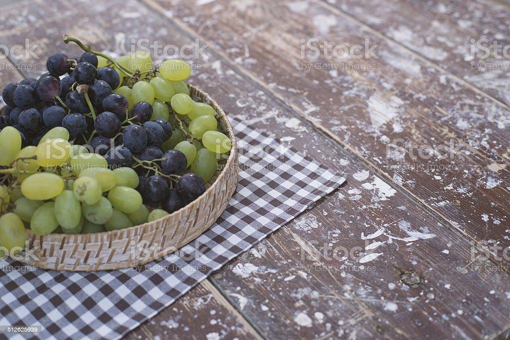 uva in un cestino su un tavolo di legno stock photo