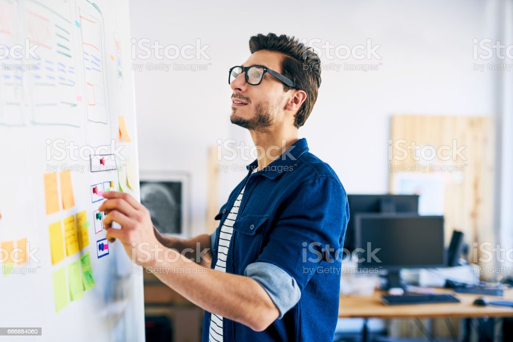 Ux specialist designing new application layout on whiteboard stock photo