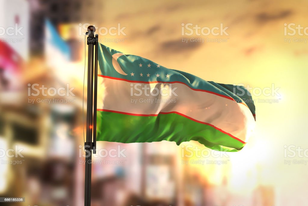 Uzbekistan Flag Against City Blurred Background At Sunrise Backlight stock photo