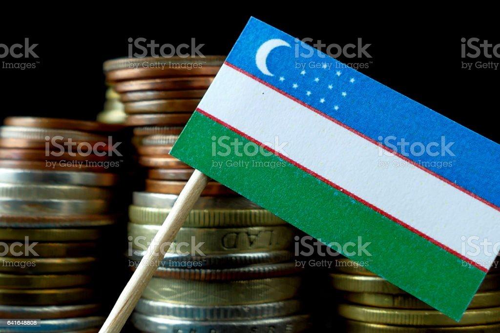 Uzbekistan flag waving with stack of money coins macro stock photo