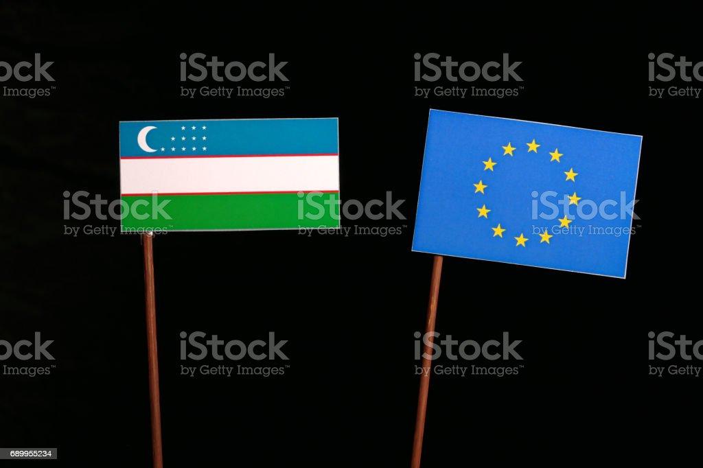 Uzbekistan flag with European Union (EU) flag isolated on black background stock photo
