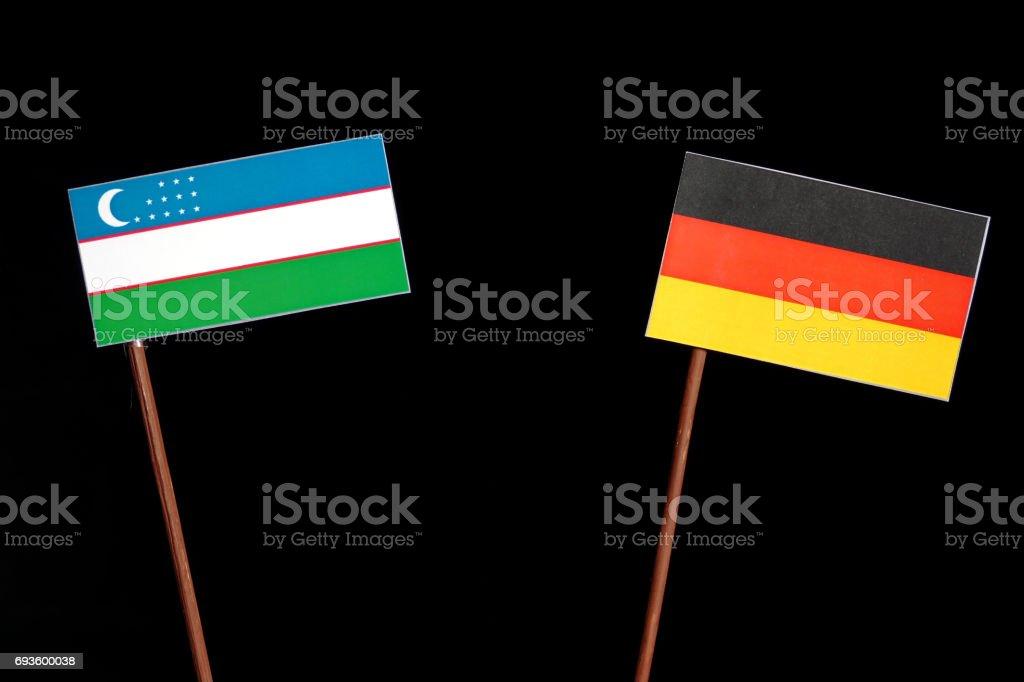 Uzbekistan flag with German flag isolated on black background stock photo