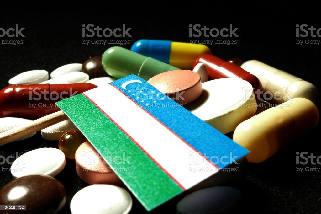 Uzbekistan flag with lot of medical pills isolated stock photo