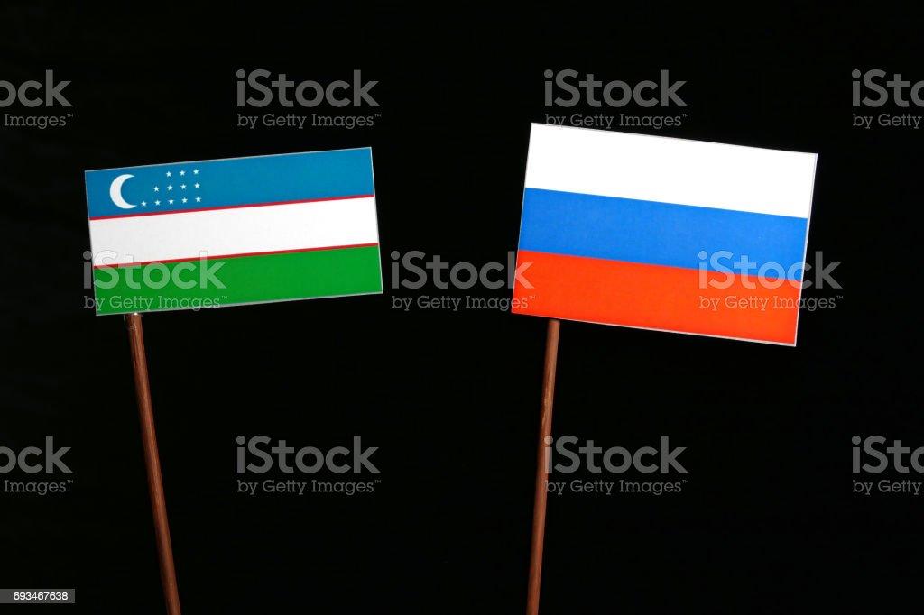 Uzbekistan flag with Russian flag isolated on black background stock photo