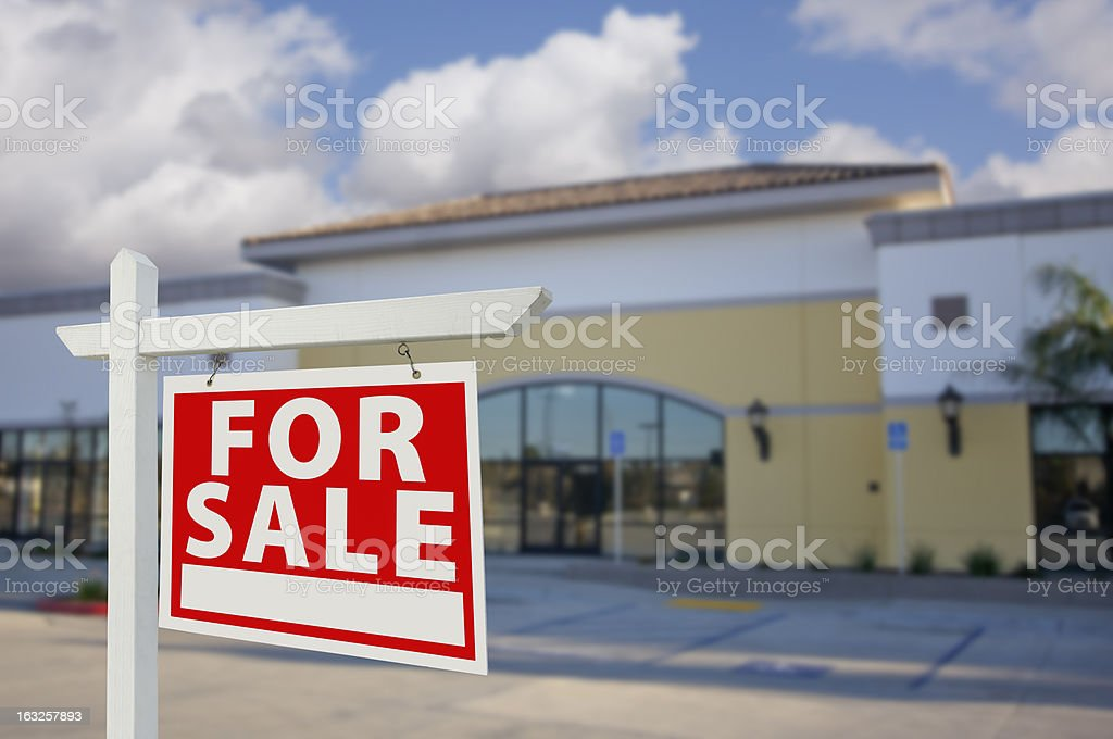 Vacant Retail Building with For Sale Real Estate Sign stock photo