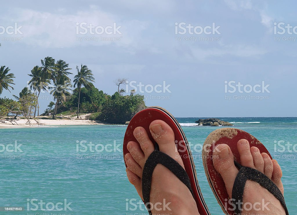Vacation concept, feet against the view of small tropical island royalty-free stock photo