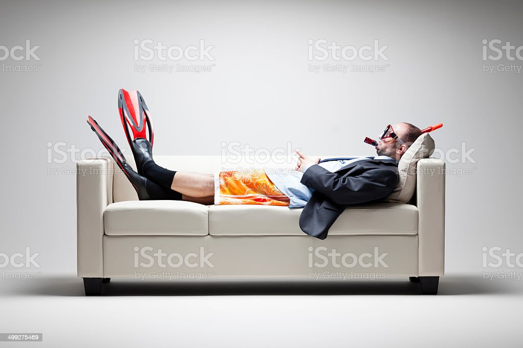 Vacation desparately needed - Businessman Couch Snorkel Swim suit stock photo