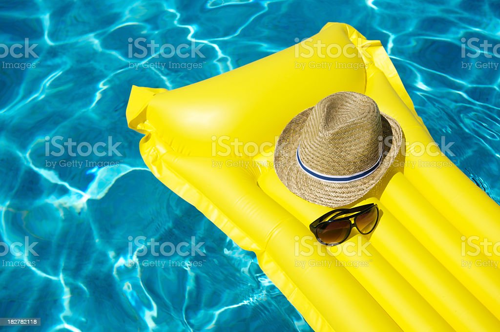 Vacation Hat and Sunglasses Floating on Yellow Pool Raft stock photo