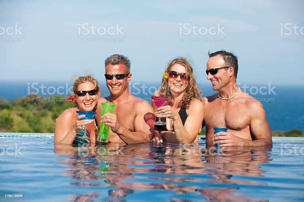 Vacation Lifestyles- Friends Laughing Together in the Pool royalty-free stock photo