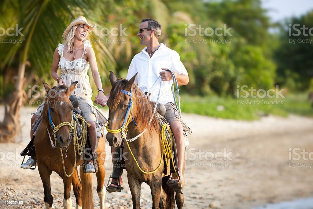 Vacation Lifestyles-Couple Riding Horses on Beach at Sunset stock photo