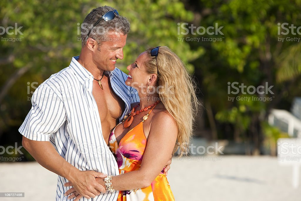 Vacation Lifestyles-Loving Couple on the Beach at Sunset royalty-free stock photo