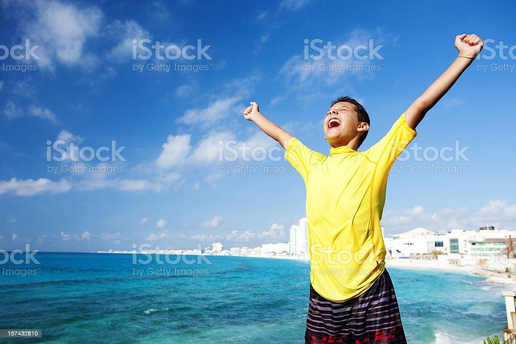 Vacation Lifestyles-Triumphant Boy at Beach stock photo