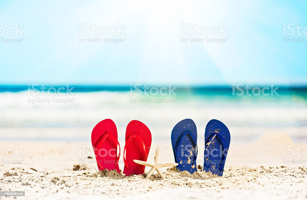 Vacation or honeymoon? His and Hers sandals on beach stock photo