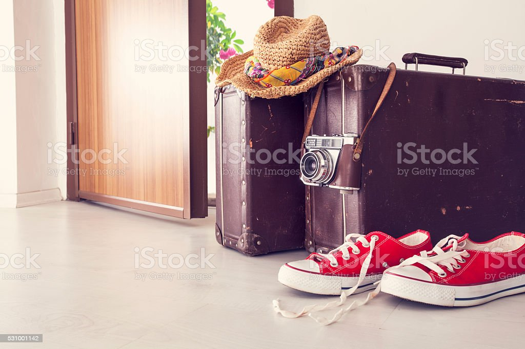 Vacation suitcase by front door stock photo