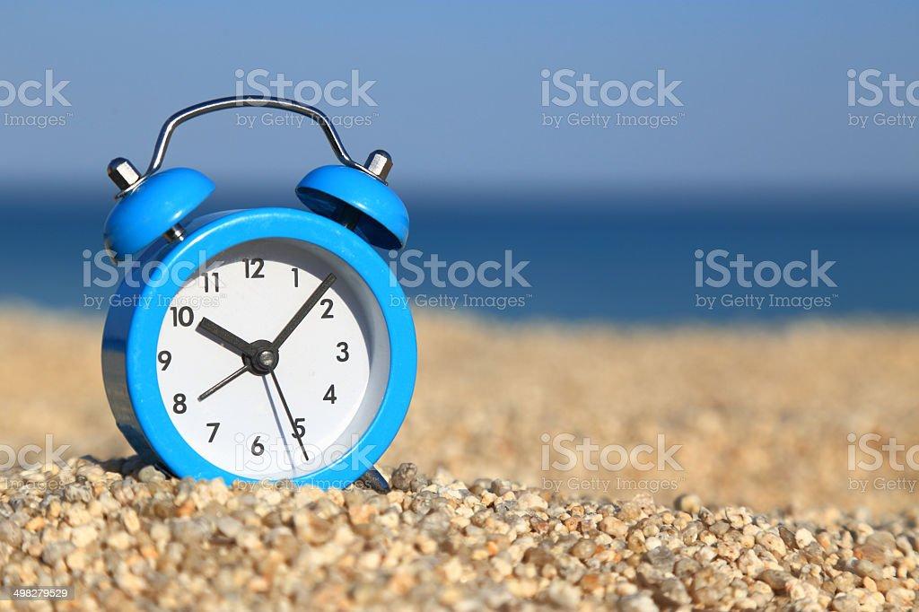 Vacation time. Alarm clock on the beach stock photo