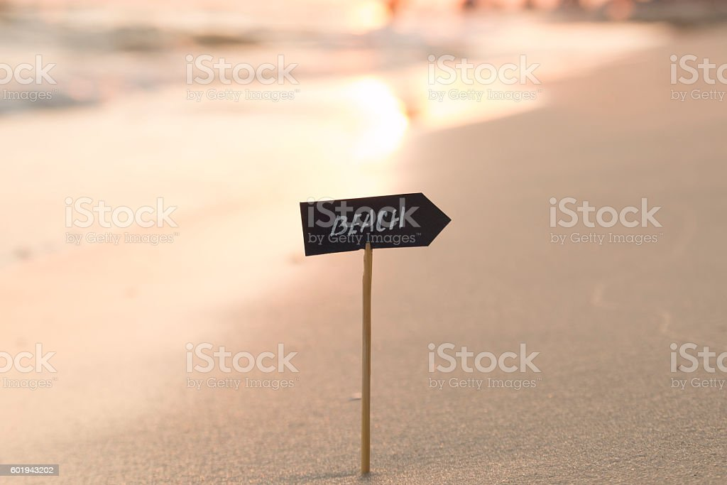 Vacation, travel or holidays idea - beach sign and sunset stock photo