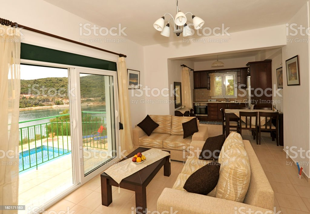 Vacation villa interior, lounge and kitchen, swimming pool views stock photo