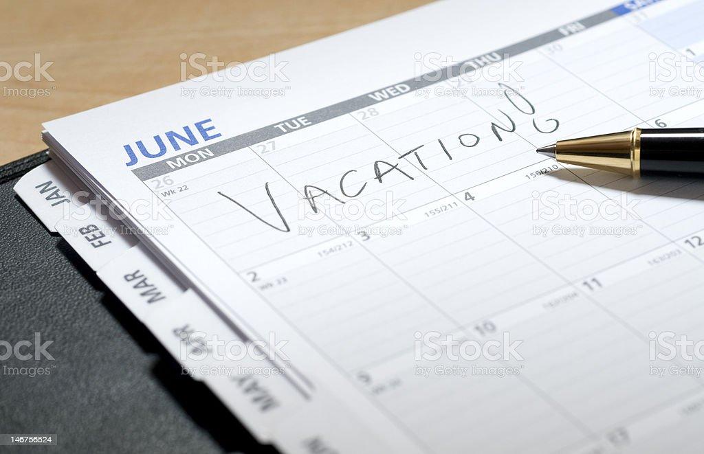 Vacances écrit sur un calendrier en juin photo libre de droits