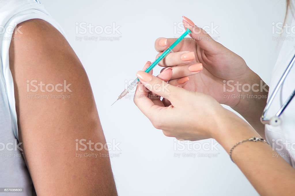 Vaccination, boy receives a vaccination in doctors office. stock photo