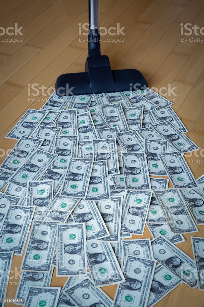 Vacuum cleaner and dollar notes stock photo