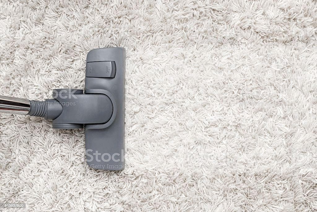 Vacuum cleaner cleans the white shaggy carpet. stock photo