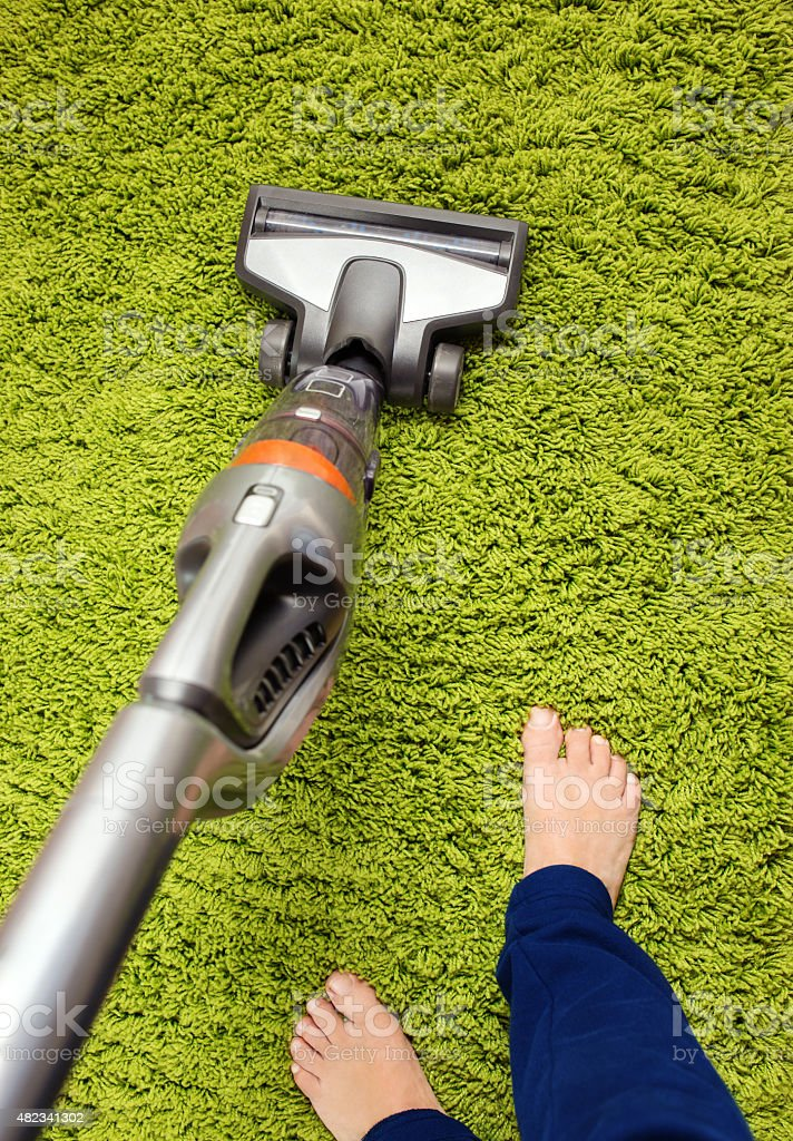 Vacuum cleaner in action - a men cleaner a carpet stock photo