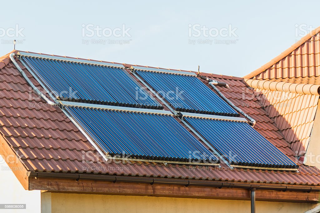 Vacuum collectors- solar water heating system on red roof of stock photo