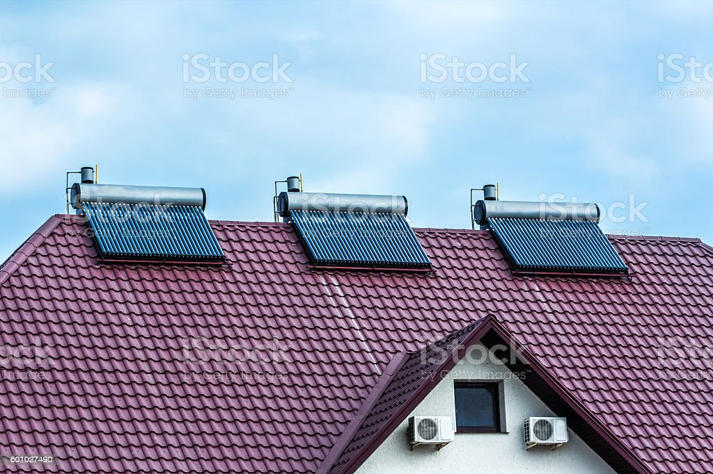 Vacuum collectors- solar water heating system on red roof stock photo